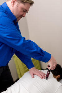 Dr. Yeager performing chiropractic Activator adjustment.